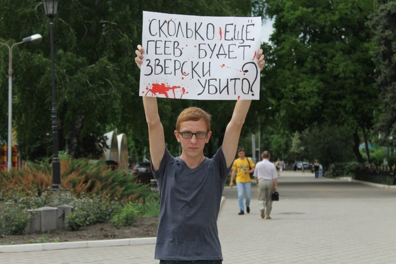 """Andrew Nasonov at a May 2013 protest following the anti-gay murder23-year-old Vladislav Tornovoi in Volgograd. His sign reads: """"How many more gays will be brutally murdered?"""""""