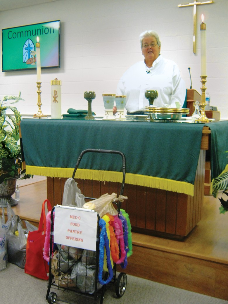 The Rev. Catherine Houchins receives donations to the church food bank during services Sept. 13 at MCC's new location on Orr Road.