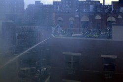 Through the smoke across the courtyard, New York City firefighters hose down rubble from rooftops above after two buildings collapsed on Park Ave. and 116th Street in New York City, March 12, 2014. (Gordon Donovan/Yahoo News)