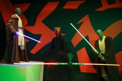 Darth Maul, the terrifying villain of Episode I, wears black, layered, kimono-style underrobes. The costume has varying lengths of split tabs, allowing for a great deal of movement during his extensive, complex fight sequences. Its many shoulder-to-ankle circular pieces were pleated, creating a narrow silhouette when motionless. In combat, however, they swirl out into a fully circular shape, like a fabric Shuriken (Ninja blade) cutting through the air. (Gordon Donovan/Yahoo News)