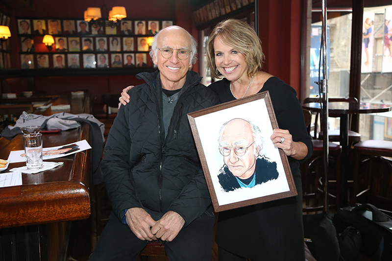 Yahoo Global News Anchor Katie Couric holds a caricature of comedian, writer and actor Larry David following an interview at Sardis in New York City, Monday Feb.16, 2015. (Gordon Donovan/Yahoo News)