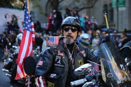 A veterans carries a flag in his teeth while riding his motorcycle during the Veterans Day parade on Fifth Avenue in New York on Nov. 11, 2016. (Gordon Donovan)