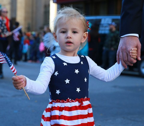 A young girl holds dad's hand as she waves a flag and marches in the Veterans Day parade on Fifth Avenue in New York on Nov. 11, 2016. (Gordon Donovan/Yahoo News)