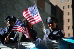 Police officers wave flags on a float during the Veterans Day parade on Fifth Avenue in New York City on Nov. 11, 2016. (Gordon Donovan/Yahoo News)