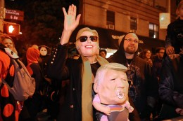 A woman wears a Hollary Clinton mask while holding a baby in a Trump mask in the 43rd annual Village Halloween Parade in New York City on Monday, Oct. 31, 2016. (Gordon Donovan/Yahoo News)