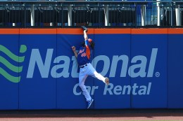 New York Mets pitcher Jacob deGrom (48) leaps up and crashes into outfield wall making a catch during batting practice before the baseball game against the Miami Marlins at Citi Field in New York, Tuesday, July 5, 2016. (Gordon Donovan)