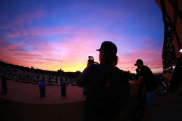 A fan uses his mobile device to take a photo the sunset on the left field stairs at Citi Field during the baseball game between the Washington Nationals and New York Mets on Friday, Sept. 2, 2016. (Gordon Donovan)