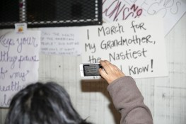 People examine discarded signs from Women's March in New York City on Jan. 21, 2017. (Gordon Donovan/Yahoo News)