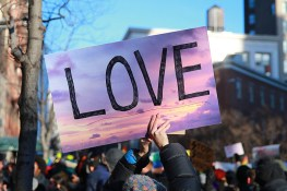 "A woman holds up a ""Love"" sign at a rally in front of the Stonewall Inn in solidarity with immigrants, asylum seekers, refugees, and the LGBT community, Feb. 4, 2017 in New York. (Photo: Gordon Donovan/Yahoo News)"