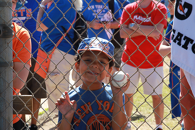 A young fan stands behind a fence looking for an autograph from a player during morning workouts at the New York Mets spring training facility in Port St. Lucie, Fl., Sunday, Feb. 26, 2017. (Gordon Donovan/Yahoo Sports)