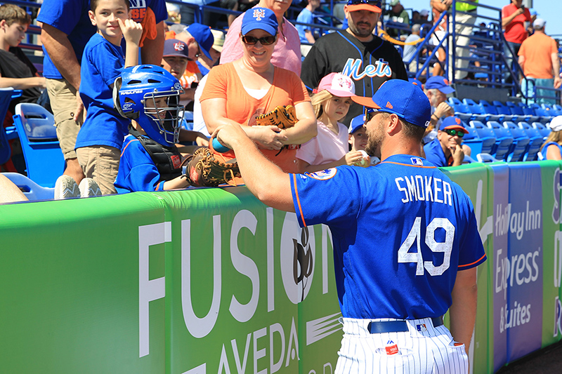 New York Mets pitcher Josh Smoker hands a ball and chats with a young fan wearing catcher's equipment in the seats before the baseball game against the Detroit Tigers at First Data Field in Port St. Lucie, Fl., Sunday, Feb. 26, 2017. (Gordon Donovan/Yahoo Sports)