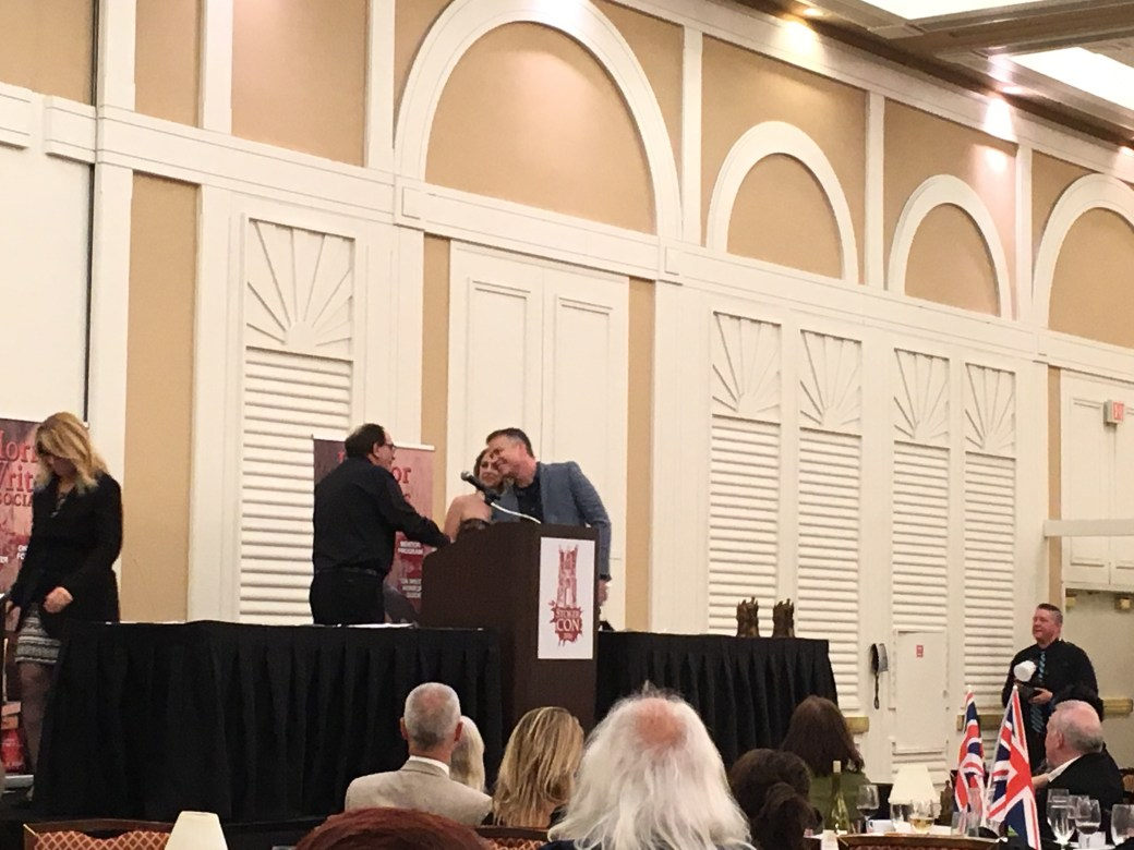 R.L. Stine shakes John Dixon's hand for winning the YA Stoker award.