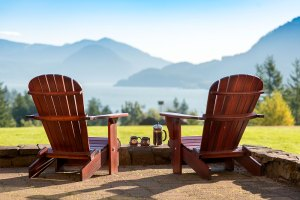 Picture of the back of two empty adirondack chairs on the front lawn of Skamania Lodge looking out at a dramatic view of the Columbia River. A carafe of coffee and two mugs sits on a rock wall in front of them.