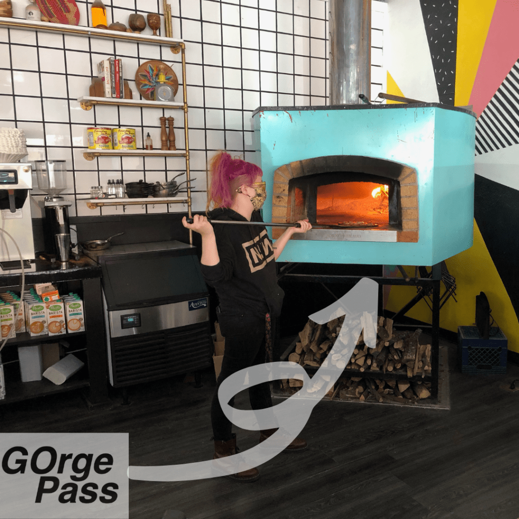Photo of a woman with pink hair and a black jacket placing a pizza into a turquoise wood fire oven. Text over the top reads GOrge Pass and includes a white swirly arrow.