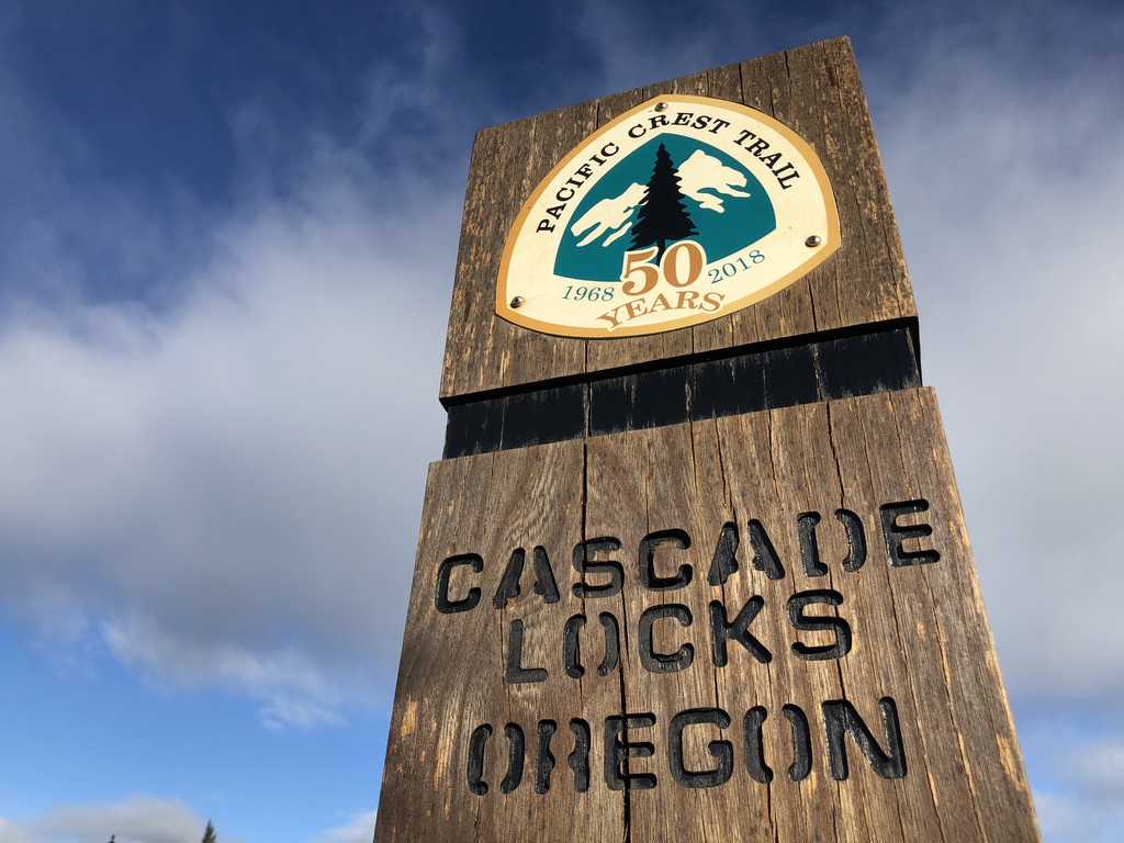 Large wood block sign post against blue sky that reads Pacific Crest Trail 50 Years 1968 - 2018 Cascade Locks Oregon