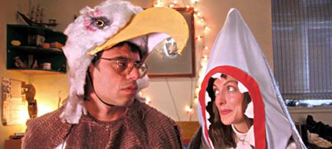 Jemaine Clement, disfrazado de águila, resistiendose a los encantos de Loren Horsley en su atuendo tiburonil