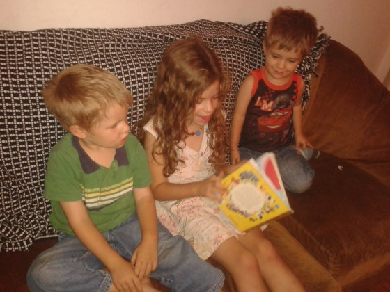 07-the girls reading to the boys on the couch