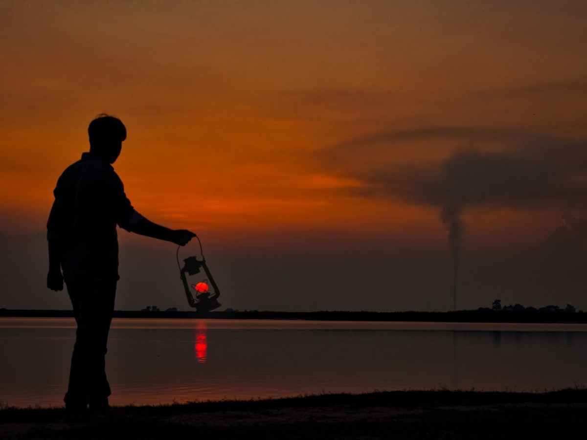 silhouette of man with oil lamp on shore at sunset