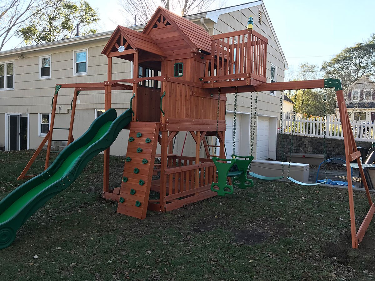wooden swing set with slide assembled by Handyman Got a Hand