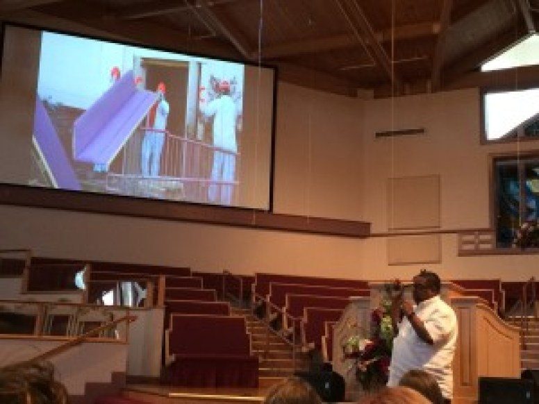 Pastor Mack showing us images of the church after the hurricane.