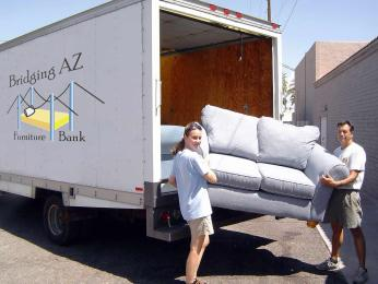 Bridging AZ Furniture Bank founders unloading a sofa from a truck.