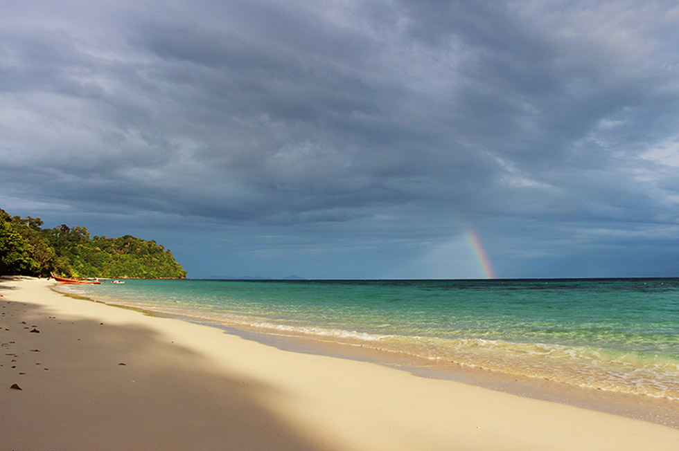 Sunset on the beach with a rainbow