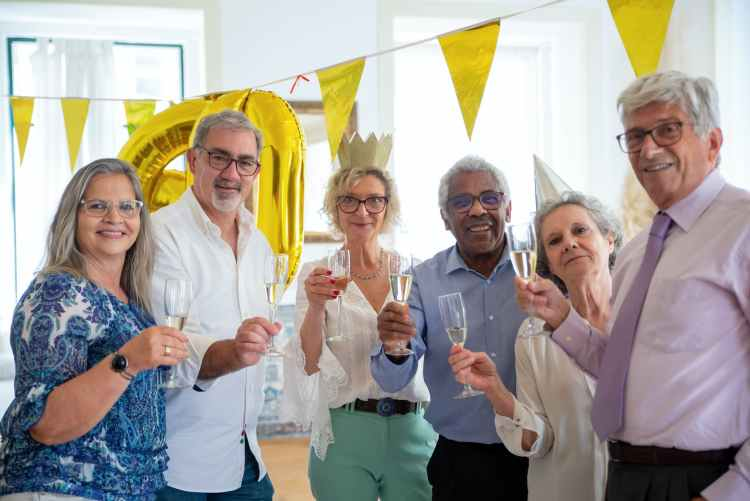 elderly people holding champagne glasses while looking at camera