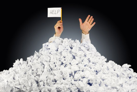 Person under crumpled pile of papers with hand holding a help sign