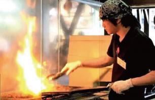オープンキッチンでカルビを網焼き
