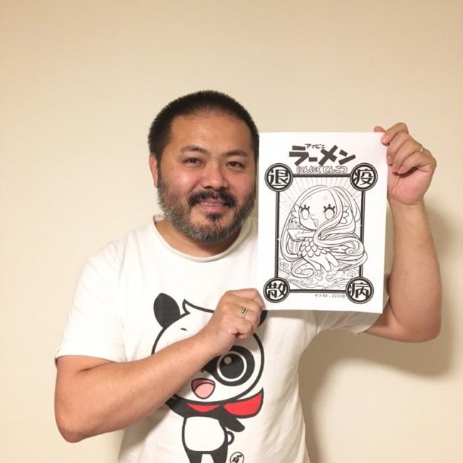 自らデザインしたアマビエを掲げる谷口氏