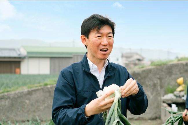 新玉ねぎを丸かじりする高村祐輝代表取締役社長