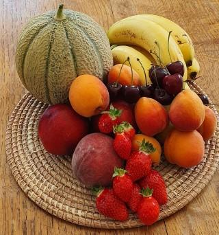 Corbeille de fruits avec un melon des bananes des abricots des fraises des pêches et des cerises