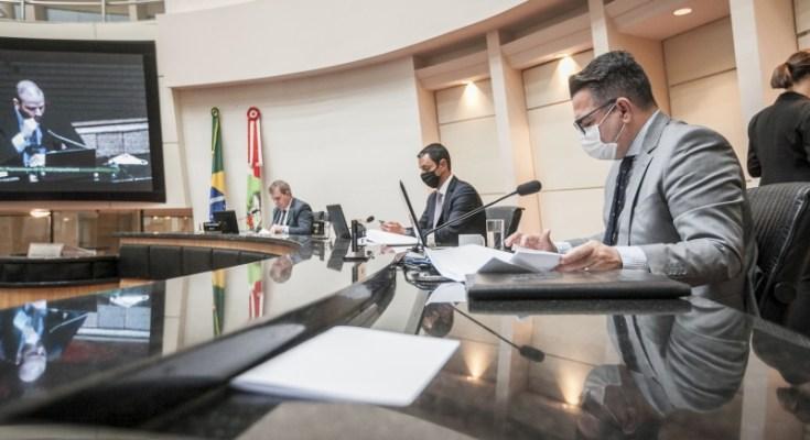 Relator Luiz Fernando Vampiro (primeiro plano) e relator-adjunto Jessé Lopes (no telão), durante a leitura do relatório da comissão do impeachment