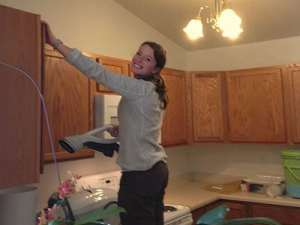 Young woman on ladder in kitchen