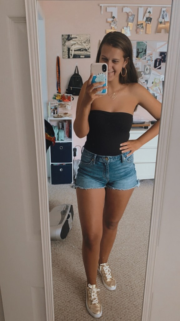 Wearing a black bodysuit, denim shorts, and gold accessories