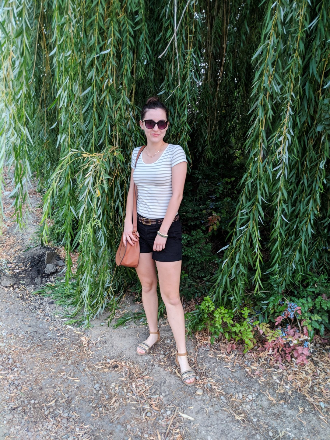 green striped tee, black shorts, brown sandals