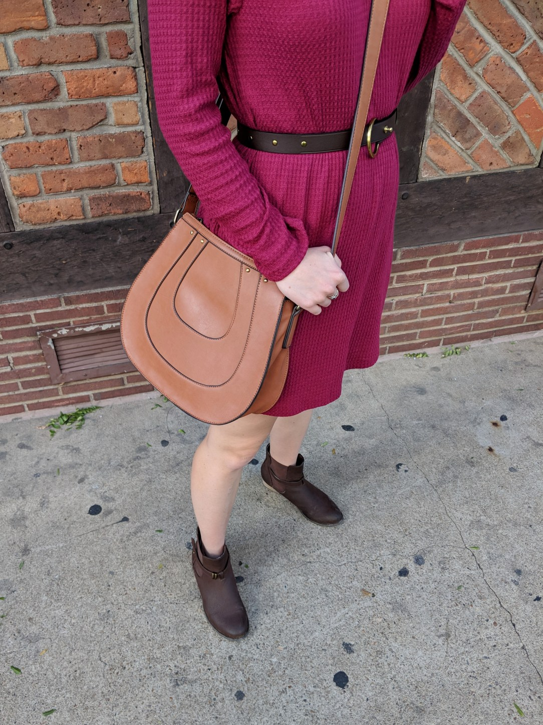 close-up of red waffle knit fabric and brown Club Monaco saddle bag
