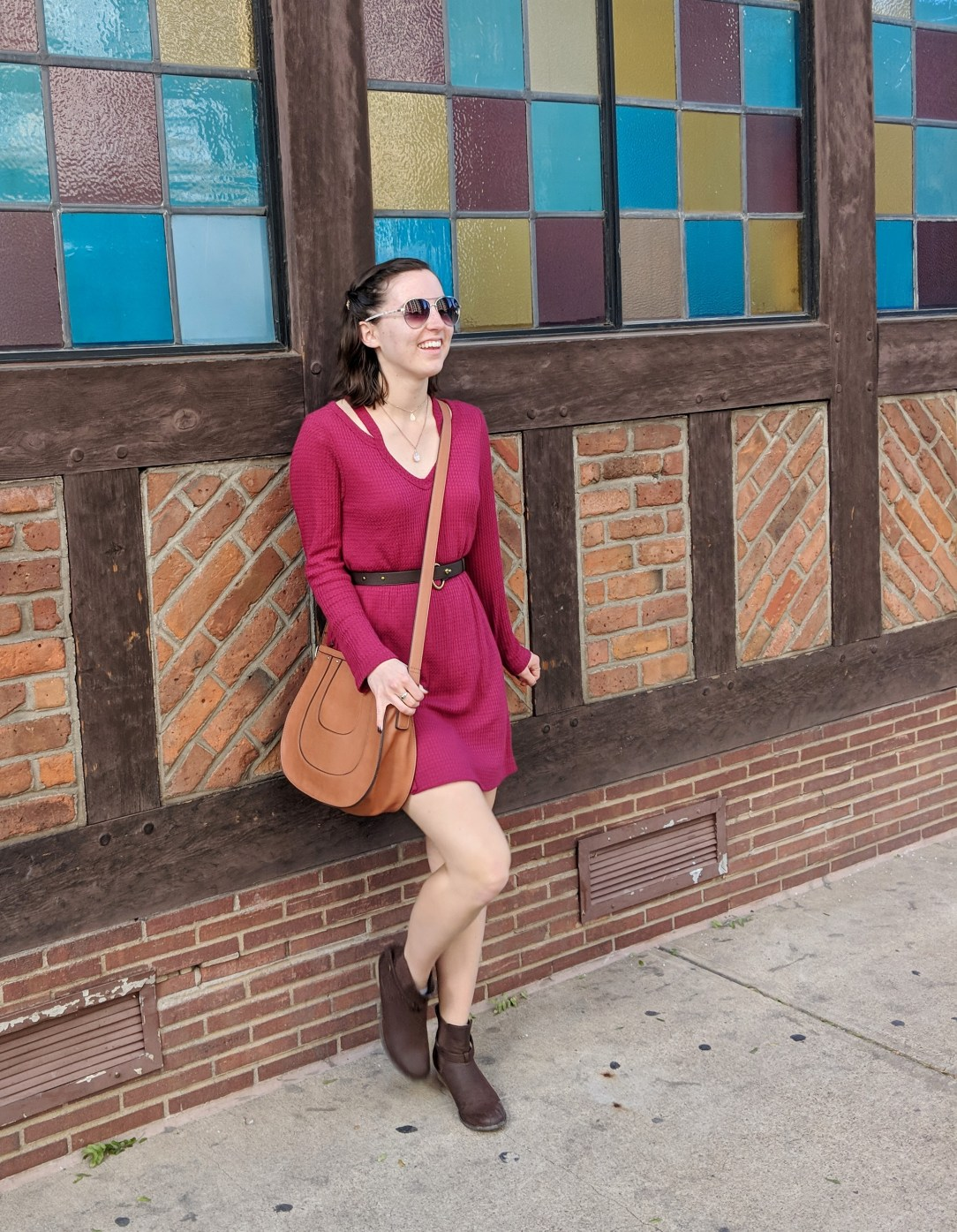 fashionista in a red dress leaning against a brick wall