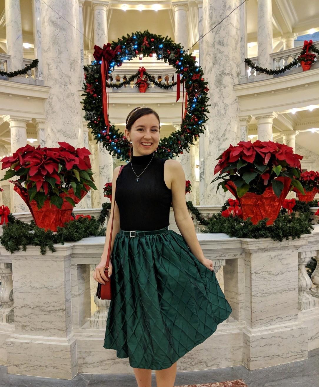 green skirt black mock neck top wreath