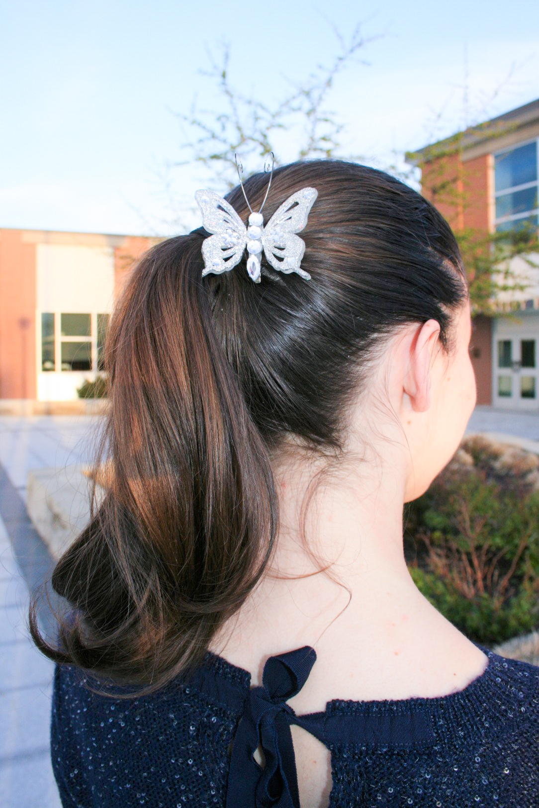 curly pony tail, butterfly hair clip, navy sweater