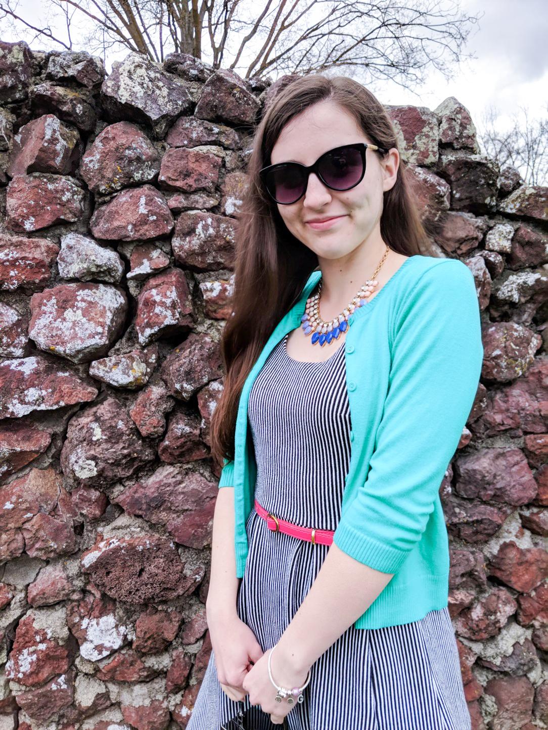 green cardigan, pink belt, statement necklace, black sunglasses