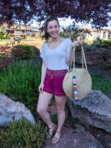 pink lounge shorts, brown sandals, wicker beach bag
