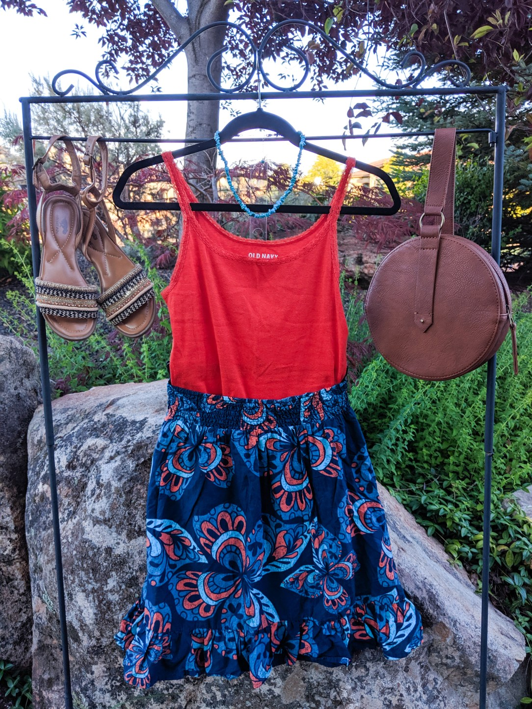 orange top, blue patterned skirt, brown accessories