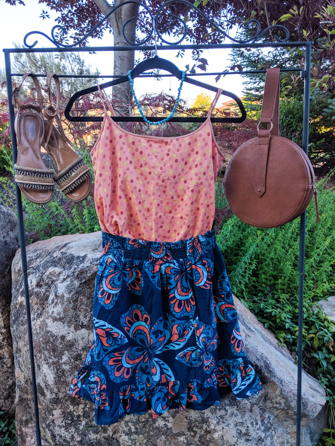 orange polka dot top, blue patterned skirt, brown accessories