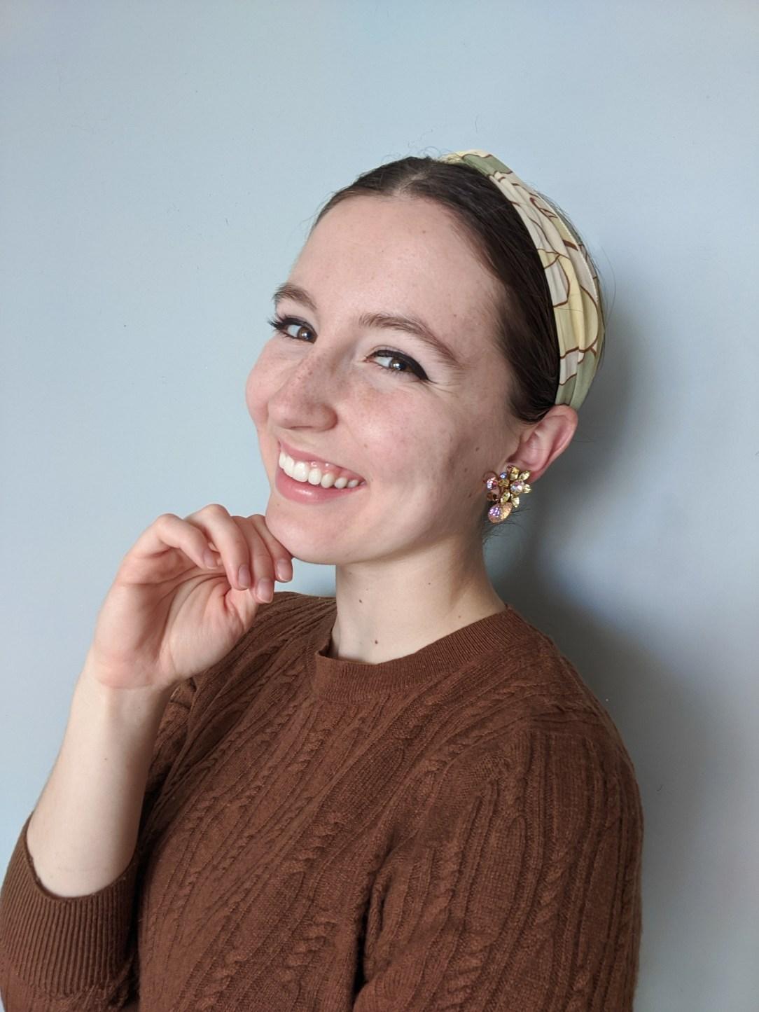 green hair scarf, brown sweater, statement earrings, winged eyeliner