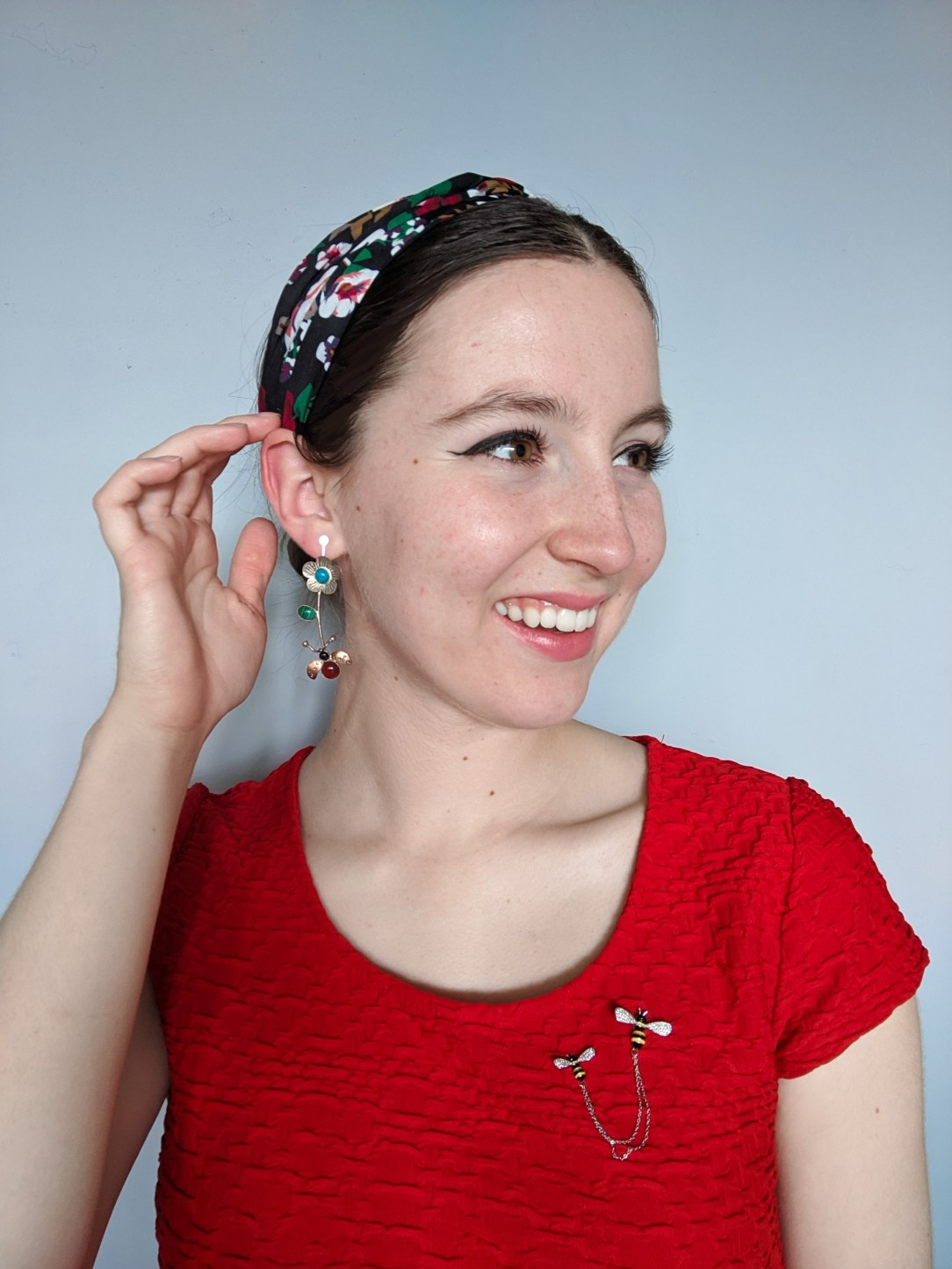 red blouse, bee pins, floral headband, statement earrings