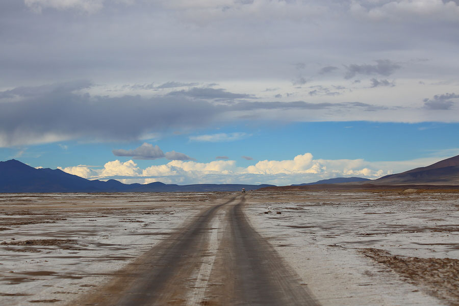 A road through the desert with mountains in the far distance.