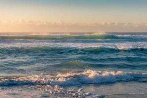 Ocean waves backlit by the sunris.