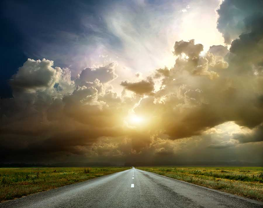 A road extends into the distance, under storm clouds and bright sunlight.