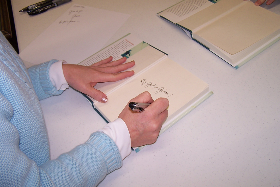 """Gracia Burnham signing copies of her book """"In the Presence of My Enemies"""". It's only possible with God's grace!"""